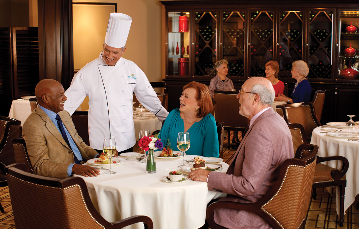 Chef speaking with residents in an upscale dining room