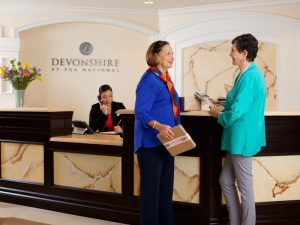 Two women talking in front of reception desk